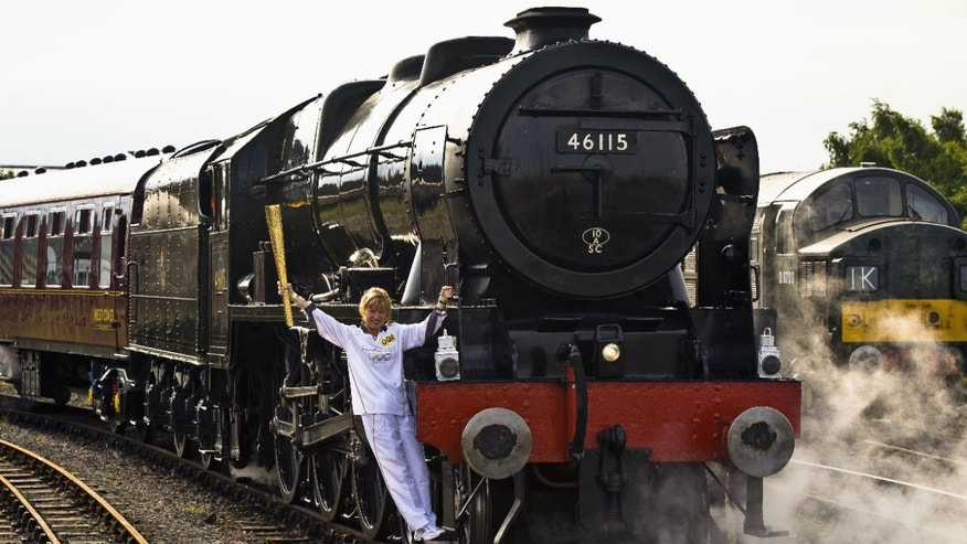 June 20, 2012: Josephine Loughran carrying the Olympic Flame on the Scots Guardsman steam locomotive as they make the journey from York to Thirsk in England on day 33 of the torch relay (AP Photo/Ben Birchall, LOCOG, HO)
