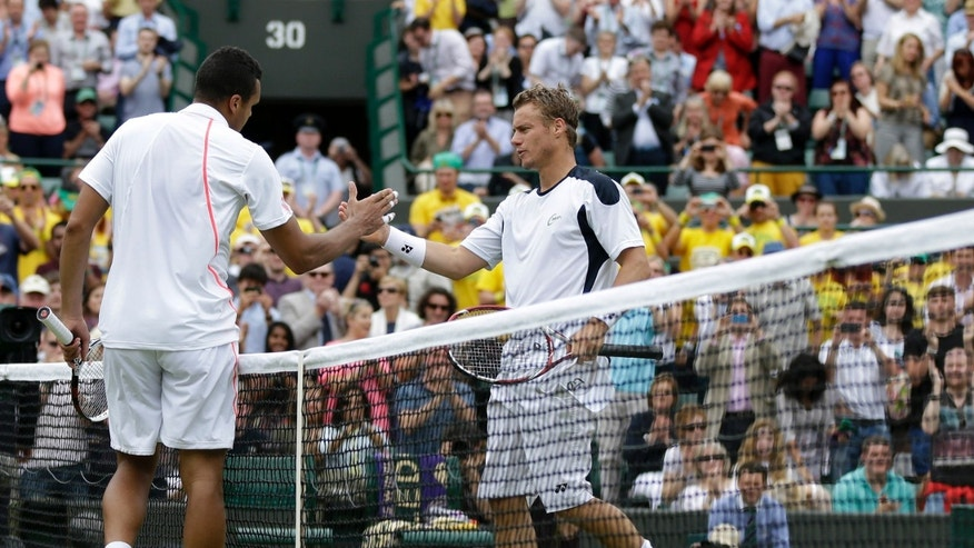 June 26, 2012: Jo-Wilfried Tsonga of France, left, shakes hands with Lleyton Hewitt of Australia after defeating him during a first round men's singles match at the All England Lawn Tennis Championships at Wimbledon, England.