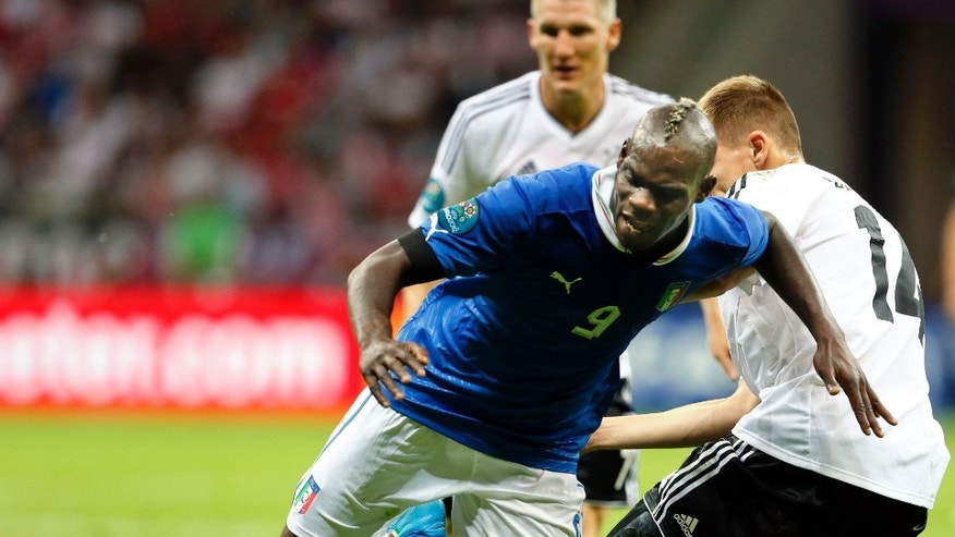 Italy's Mario Balotelli is tackled by Germany's Holger Badstuber during the Euro 2012 soccer championship semifinal match between Germany and Italy in Warsaw, Poland, Thursday, June 28, 2012. (AP Photo/Gregorio Borgia)