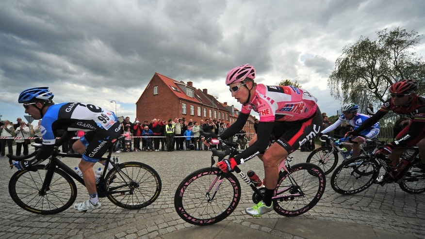 May 7, 2012: In this file photo, Taylor Phinney, second from left, of the United States, wears the overall leader's pink jersey as he rides through a corner during the third stage of the Giro d'Italia cycling race in Horsens, Denmark.