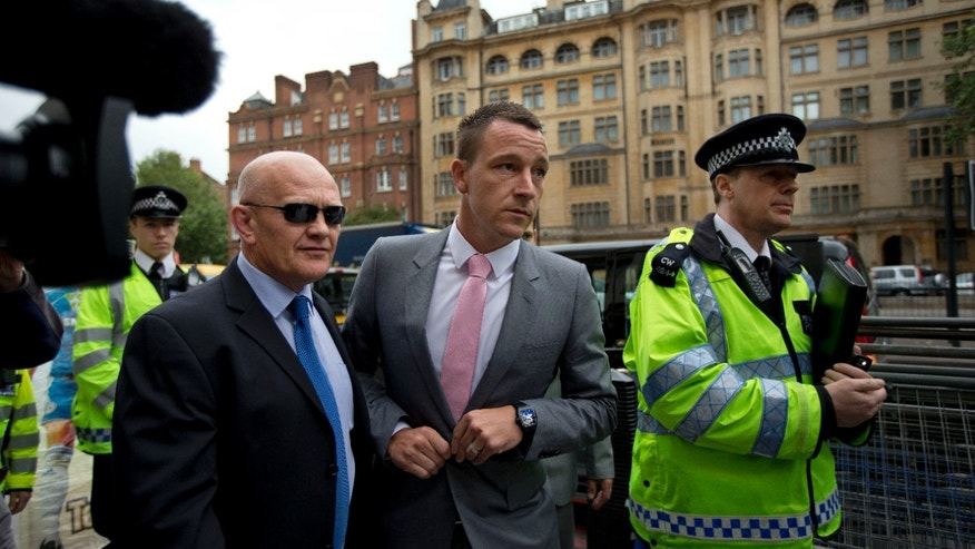 July 9, 2012: Former England football captain and current Chelsea player John Terry, center, arrives at Westminster Magistrates Court, London.