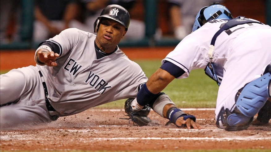 New York Yankees' Robinson Cano, left, is tagged out by Tampa Bay Rays catcher Jose Molina during the sixth inning of a baseball game Tuesday, July 3, 2012, in St. Petersburg, Fla. (AP Photo/Mike Carlson)