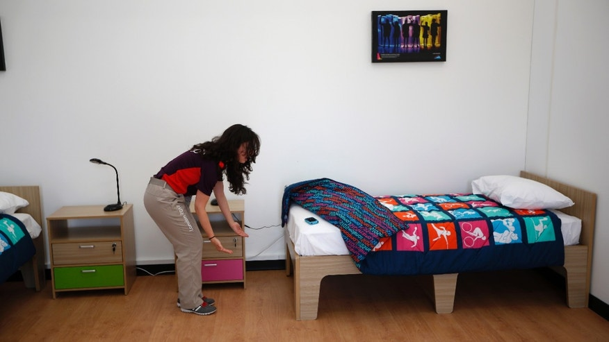July 12, 2012: An Olympic volunteer shows with her hands an approximation of how much further the length of a standard bed could be extended in length for taller athletes in a display bedroom, that was larger that the real room athletes will have, during a media opportunity at the Olympic and Paralympic athlete's village in London.