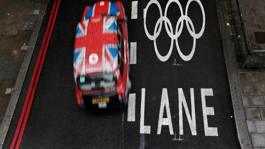 July 16, 2012: A taxi cab drives past an Olympic lane on a street as the city prepares for the 2012 Summer Olympics, central London.