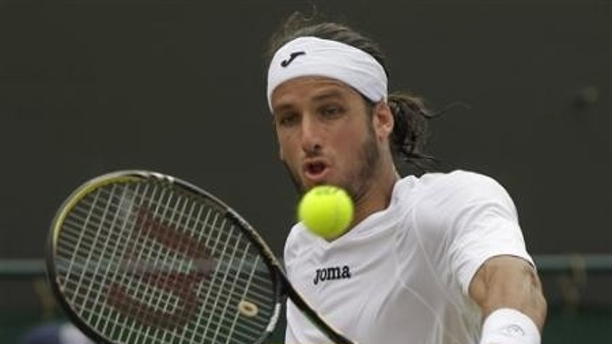 June 27, 2011:Spain's Feliciano Lopez returns a shot to Poland's Lukasz Kubot at the All England Lawn Tennis Championships at Wimbledon.