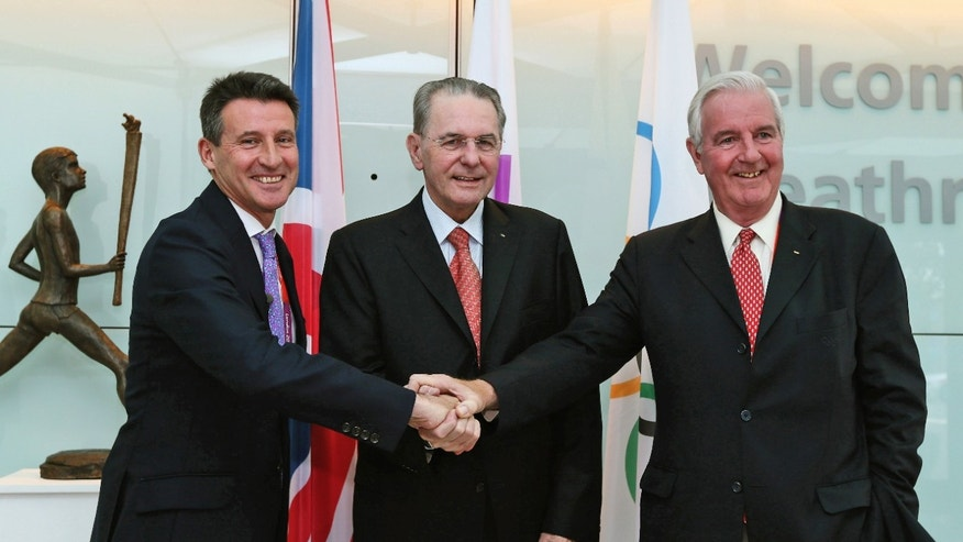 July 20, 2012: IOC President Jacques Rogge, center, is welcomed by London 2012 Olympic games chairman Sebastian Coe, right, and the IOC member for Great Britain Craig Reedie on his arrival for the London 2012 Olympic Games at Heathrow Airport in London, England.