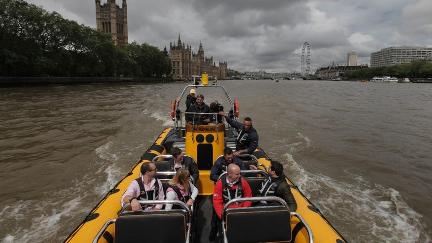 July 4, 2012: In this photo, people are seen aboard a high-speed 12-seater rigid inflatable boat, run by the Protection Services International company as it travels past the Palace of Westminster on London's river Thames.