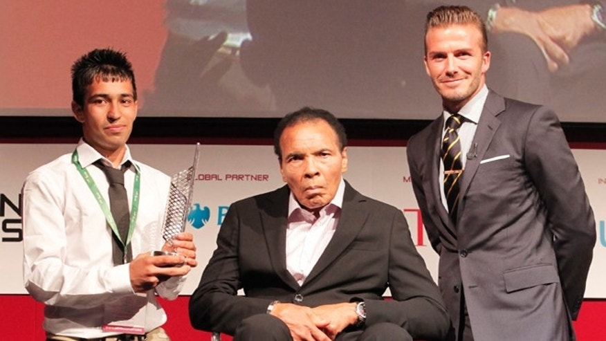 July 24, 2012: Boxing legend Muhammad Ali, center, with soccer player David Beckham, right, presenting a community service award to Matiullah Haidar at the Beyond Sport Summit in London.
