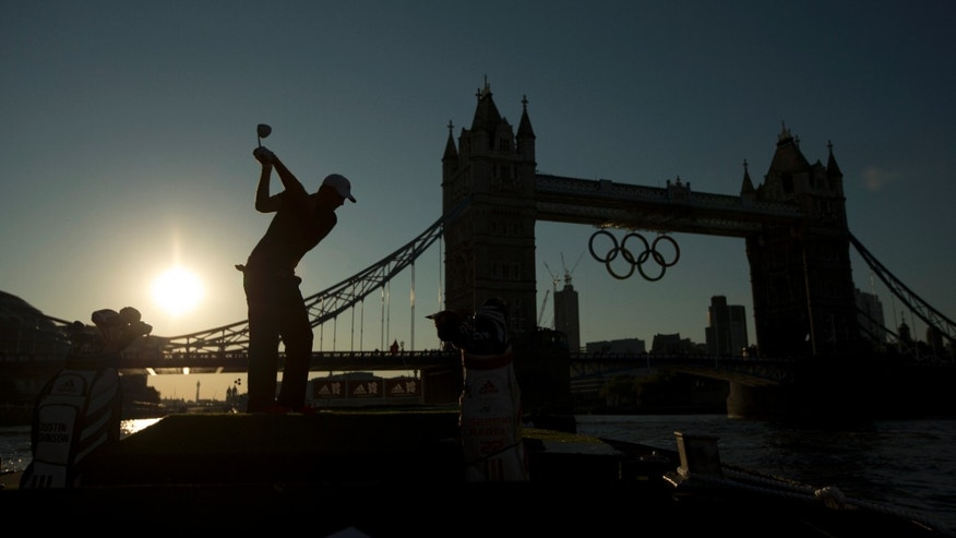 U.S. golfer Dustin Johnson is silhouetted as he takes a swing in a posed picture for photographers as Olympic rings hang from Tower Bridge.