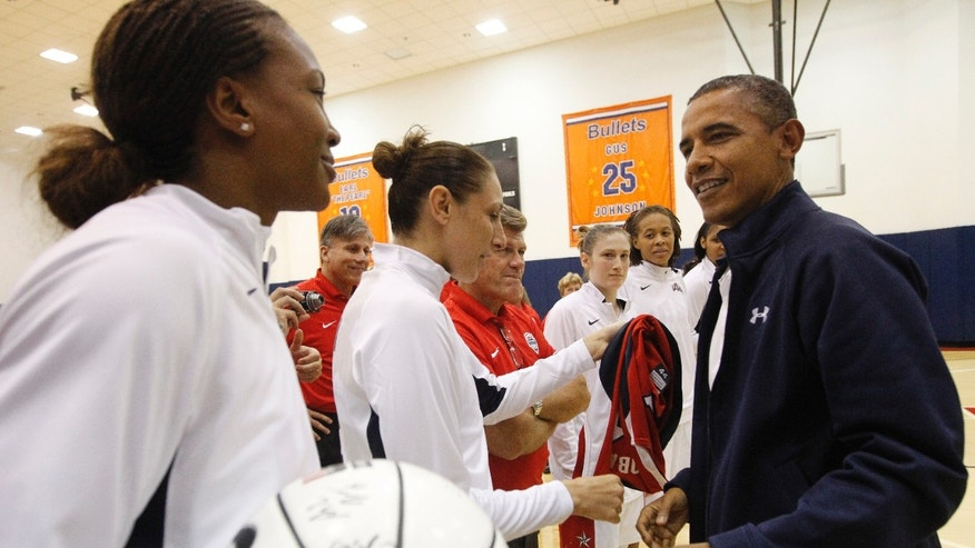 July 16, 2012: President Barack Obama, right, meets with Team USA's Tamika Catchings, left, and Diana Taurasi, center, and other members of the Olympic women's basketball following their exhibition game against Brazil in Washington.