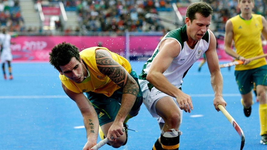 Australia's Kieran Govers, left, shoots towards the goal as South Africa's Andrew Cronje defends during a men's field hockey preliminary match at the 2012 Summer Olympics, Monday, July 30, 2012, in London. (AP Photo/Bullit Marquez)