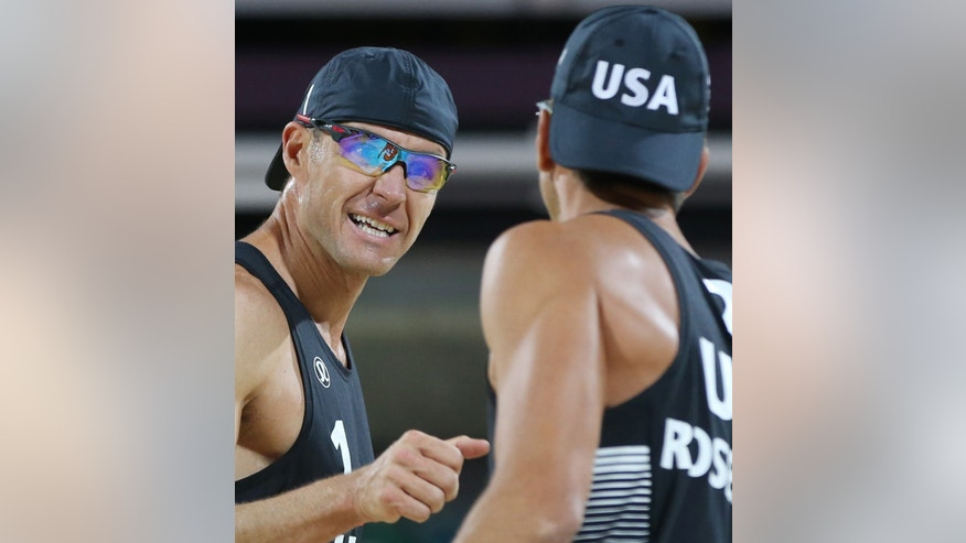 Jake Gibb, left, of US celebrates with his teammate Sean Rosenthal, right, during their Beach Volleyball match against  South Africa at the 2012 Summer Olympics, Saturday, July 28, 2012, in London. (AP Photo/Petr David Josek)