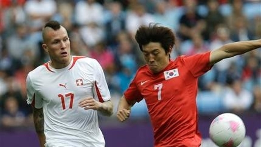 July 29, 2012: South Korea's Kim Bok-yung, right, battles for the ball against Switzerland's Michel Morganella at the London 2012 Summer Olympics.