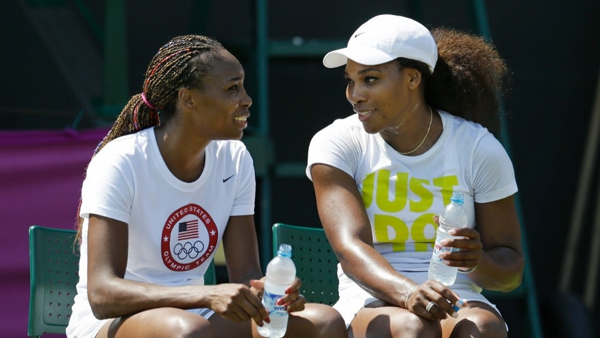 Venus, left, and Serena Williams, of the United States, talk during a break in practice at the All England Lawn Tennis Club at Wimbledon, in London, at the 2012 Summer Olympics, Thursday, July 26, 2012. Tennis competition is scheduled to begin Saturday, July 28. (AP Photo/Mark Humphrey)