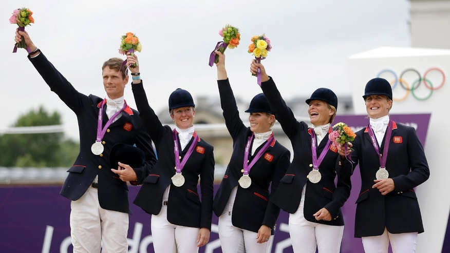 July 31, 2012: Members of the British equestrian eventing team, from left, William Fox-Pitt, Nicola Wilson, Zara Phillips, Mary King, and Kristina Cook, wave to the crowd after receiving the silver medal in the equestrian eventing team competition at the 2012 Summer Olympics in London.
