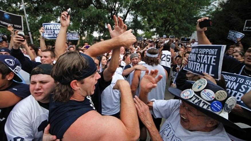 July 31, 2012: Penn State University linebacker Michael Mauti, second from left foreground, and his teammates are greeted by a pep rally of supporters on the way to a morning workout outside the Lasch Football building on the Penn State main campus in State College, Pa.