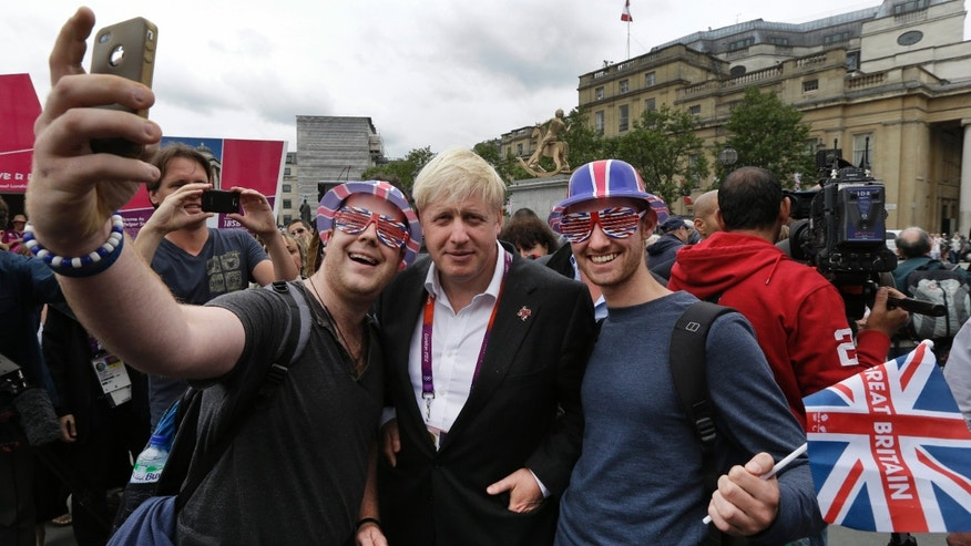 London Mayor Boris Johnson, center, poses for pictures with Britain team fans, following a photo-op with London ambassadors, the volunteers working around the city to give tourists directions and information, in central London, Tuesday, July 31, 2012. Johnson said he doesnt have eyes for top Britains leadership post - despite the unprecedented forum hes now enjoying during the Summer Olympics. (AP Photo/Lefteris Pitarakis)