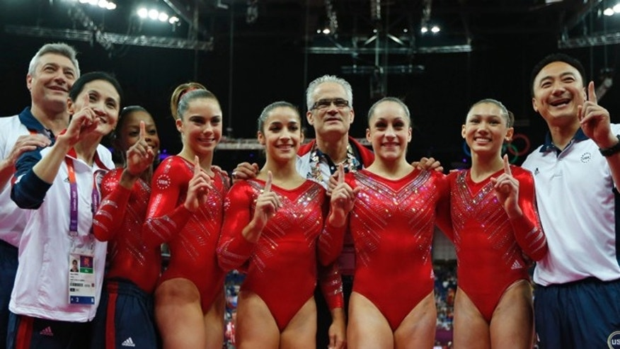 July 31, 2012: U.S. gymnasts, left to right wearing red, Gabrielle Douglas, McKayla Maroney, Alexandra Raisman, Jordyn Wieber and Kyla Ross celebrate with coaches Jenny Zhang, front left, Mihai Brestyan, back left, John Geddert, center, and Liang Chow, right, after their team won the gold medal for the Artistic Gymnastics women's team final at the 2012 Summer Olympics, in London.