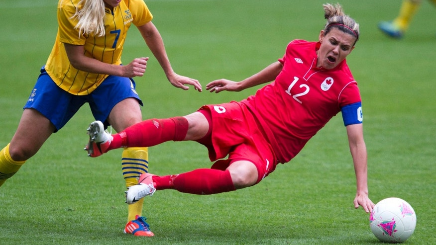 Sweden midfielder Lisa Dahlkvist (7) fouls Canada forward Christine Sinclair (12) during second half of a group F women's soccer match at St James' Park in Newcastle, England, during the London 2012 Summer Olympics, Tuesday, July 31, 2012. (AP Photo/The Canadian Press, Frank Gunn)