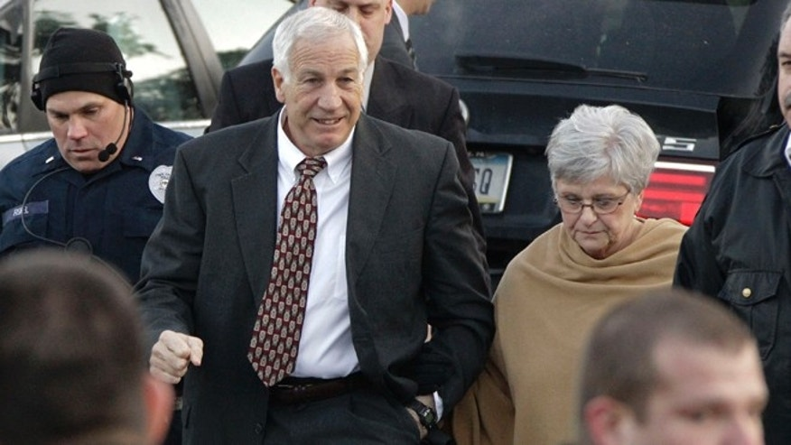 Dec. 13, 2011: In this file photo, former Penn State assistant football coach, Jerry Sandusky, center, arrives with his wife, Dottie Sandusky, right, for a preliminary hearing at the Centre County Courthouse in Bellefonte, Pa.