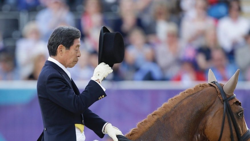 Hiroshi Hoketsu from Japan reacts as he rides Whisper in the equestrian dressage competition, at the 2012 Summer Olympics, Thursday, Aug. 2, 2012, in London. (AP Photo/Markus Schreiber)
