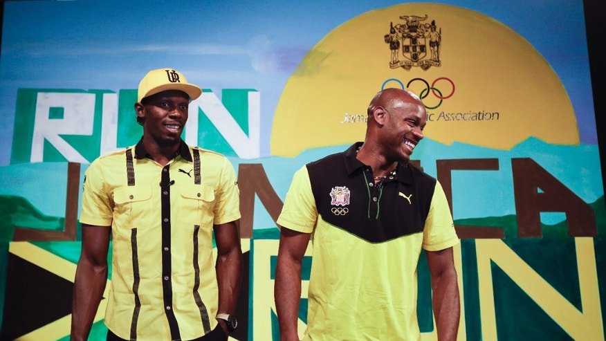 Jamaican sprinters Usain Bolt, left, and Asafa Powell, right, joke as they pose for photographers at the end of a press conference by the Jamaica Olympic Association ahead of the 2012 Summer Olympics, Thursday, July 26, 2012, in London.  The opening ceremonies for the 2012 London Olympics will be held Friday, July 27. (AP Photo/Ben Curtis)