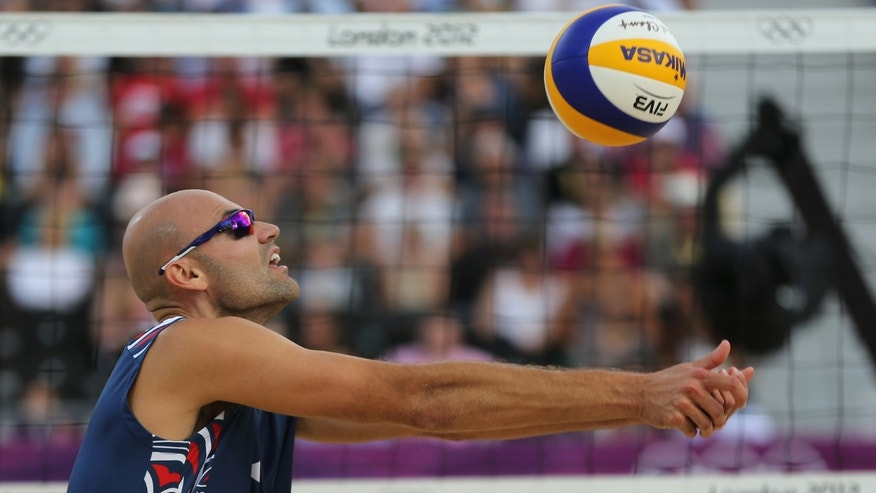 Phil Dalhausser US reaches for a ball during the Beach Volleyball match against Italy at the 2012 Summer Olympics, Friday, Aug. 3, 2012, in London. (AP Photo/Petr David Josek)