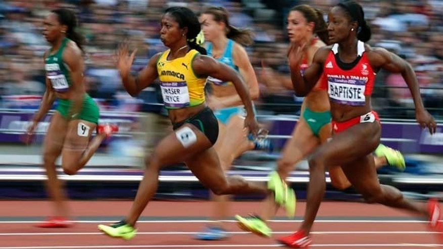 Jamaica's Shelly-Ann Fraser-Pryce, center, and Trinidad's Kelly-Ann Baptiste, right, compete in the women's 100-meter semifinal during athletics competition in the Olympic Stadium at the 2012 Summer Olympics, Saturday, Aug. 4, 2012, in London. (AP Photo/Matt Dunham)
