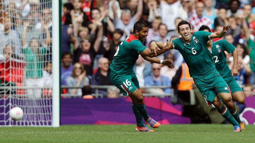Mexico's Hector Herrera (6) celebrates with teammate Mexico's Miguel Ponce (16) after his goal against  Senegal during their quarterfinal men's soccer match at the 2012 Summer Olympics, Saturday, Aug. 4, 2012, in London.  Mexico won, 4-2. (AP Photo/Marcio Jose Sanchez)