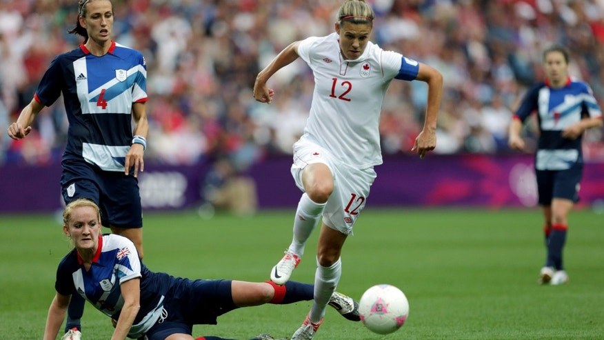 Canada's Christine Sinclair, center, avoids a tackle from Britain's Sophie Bradley, left, during their quarterfinal women's soccer match at the 2012 London Summer Olympics, in Coventry, England, Friday, Aug. 3, 2012. (AP Photo/Armando Franca)