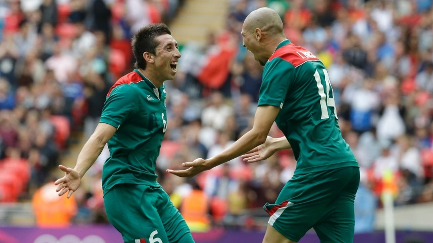 Mexico's Hector Herrera, left, celebrates with team mate Jorge Enriquez after scoring his side's third goal during their men's soccer quarterfinal match against Senegal at the 2012 Summer Olympics, Saturday, Aug. 4, 2012, in London. (AP Photo/Matthias Schrader)