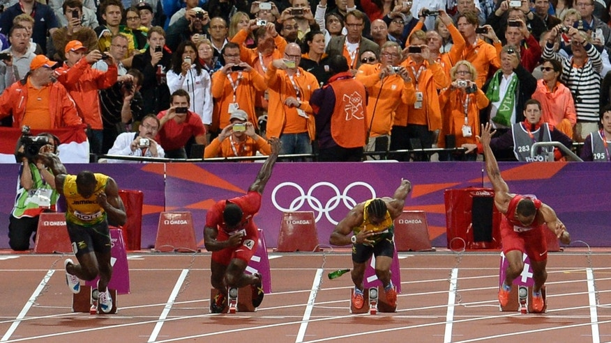 A bottle lands on the track after being thrown from the crowd as, from let, Jamaica's Usain Bolt, United States' Justin Gatlin, Jamaica's Yohan Blake, Jamaica's Yohan Blake, and United States' Tyson Gay start in the men's 100-meter final during the athletics in the Olympic Stadium at the 2012 Summer Olympics, London, Sunday, Aug. 5, 2012. (AP Photo/Martin Meissner)