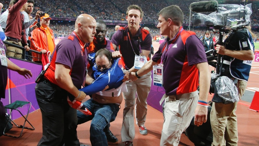 In this Sunday Aug. 6, 2012 photo, a man, identified by police as Ashley Gill-Webb, 34, is detained by security after a bottle was thrown onto the track just before the men's 100-meter final at the London 2012 Olympic Games in London August 5, 2012. Gill-Web was charged Monday Aug. 6 with a public order offense and was to appear later in custody at Stratford Magistrates Court. He was charged with intentionally causing harassment, alarm or distress, police said. (AP Photo/Chris Helgren, Pool)