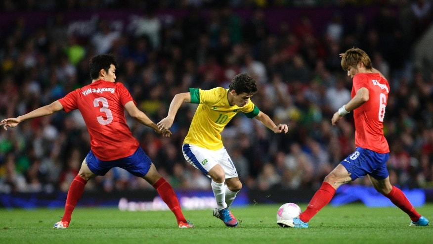 Aug. 7, 2012: Brazil's Oscar, center, fights for the ball against South Korea's Yun Suk-young, left, and Ki Sung-yueng during their semifinal men's soccer match at the 2012 London Summer Olympics at Old Trafford Stadium in Manchester, England.