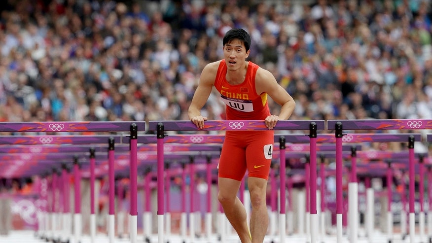 Aug. 7, 2012: China's Liu Xiang rests on a hurdle after falling in a men's 110-meter hurdles heat during the athletics in the Olympic Stadium at the 2012 Summer Olympics, London.