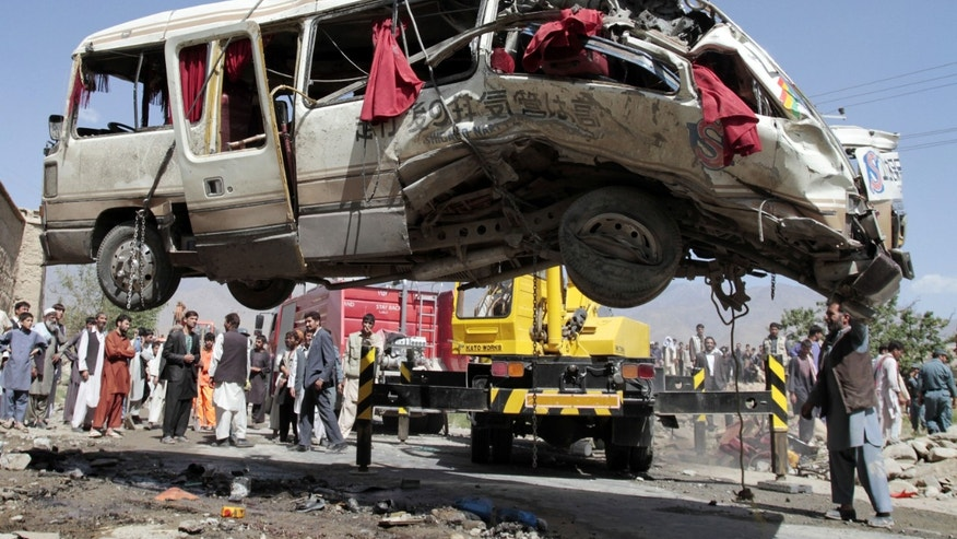 Aug. 7, 2012: A damaged bus which was hit by a remote control bomb is lifted by a crane on the outskirts of Kabul, Afghanistan.