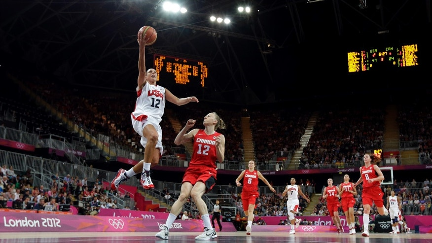 Aug. 7, 2012: USA's Diana Taurasi, left, leaps past Canada defender Lizanne Murphy (12) to score during a quarterfinal women's basketball game at the 2012 Summer Olympics, in London.