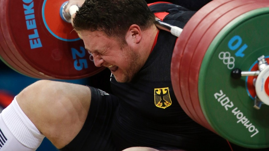 Matthias Steiner of Germany gets hit by the weights while failing to make a successful lift  in the men's over 105-kg, group A, weightlifting competition at the 2012 Summer Olympics, Tuesday, Aug. 7, 2012, in London. (AP Photo/Mike Groll)