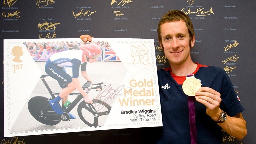 The handout photo provided by Royal Mail on Thursday, Aug. 2, 2012 shows British cyclist Bradley Wiggins with his gold medal and a new stamp celebrating his gold medal in the Men's Road Cycling Time Trial. (AP Photo/Royal Mail)