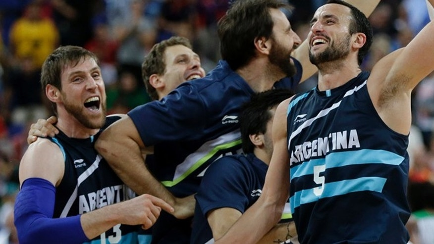 Argentina's Andres Nocioni (13) and Manu Ginobili (5) celebrate with teammates after defeating Brazil in a quarterfinal men's basketball game at the 2012 Summer Olympics, Wednesday, Aug. 8, 2012, in London. (AP Photo/Eric Gay)