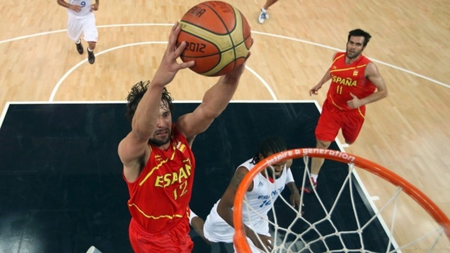 Sergio Llull (12) of Spain goes up for a dunk in front of Ronny Turiaf (14) of France during a men's basketball quarterfinal game at the 2012 Summer Olympics on Wednesday, Aug. 8, 2012, in London. (AP Photo/Christian Petersen, Pool)