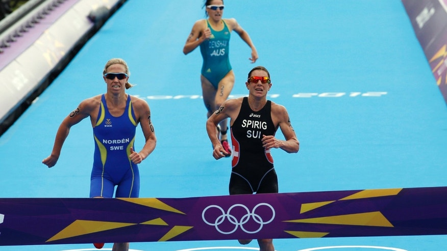 Gold-medallist Switzerland's Nicola Spirig, right, silver-medallist Sweden's Lisa Norden, left, and bronze-medallist Australia's Erin Densham compete in the triathlon at the 2012 Summer Olympics, Saturday, Aug. 4, 2012, in London. (AP Photo/Jae C. Hong)