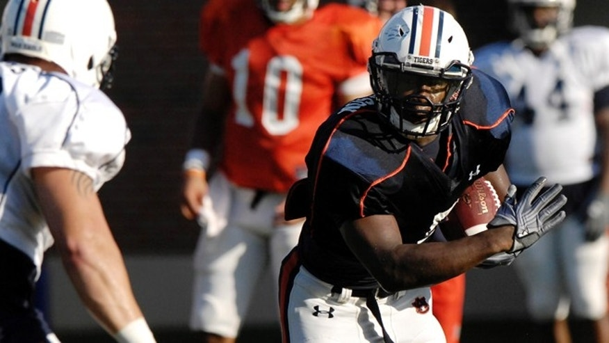 Aug. 6, 2012: Auburn running back Jovon Robinson is tackled by defender Jake Holland during NCAA college football practice on in Auburn, Ala.