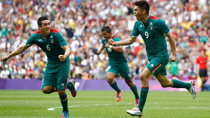 Mexico's Oribe Peralta celebrates the second goal with teammate Hector Herrera (6) during the men's soccer final against Brazil at the 2012 Summer Olympics, Saturday, Aug. 11, 2012, in London. (AP Photo/Jon Super)