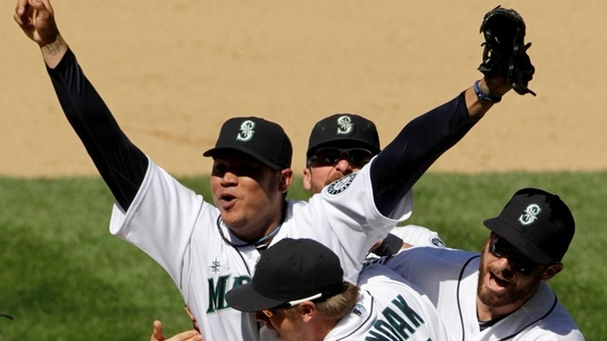 August 16: Seattle Mariners pitcher Felix Hernandez celebrates with teammates, including Justin Smoak (17), after throwing a perfect game. (AP Photo/The Seattle Times, Mark Harrison)