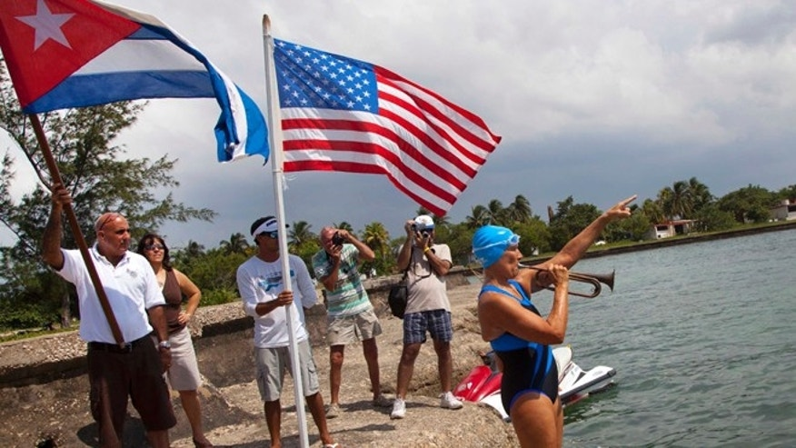 U.S. swimmer Diana Nyad plays a trumpet and points to Florida before starting her swim as people from the local nautical club hold a Cuban and U.S. flag behind her in Havana, Cuba, Saturday, Aug. 18, 2012. Endurance athlete Nyad launched another bid Saturday to set an open-water record by swimming from Havana to the Florida Keys without a protective shark cage. (AP Photo/Ramon Espinosa)
