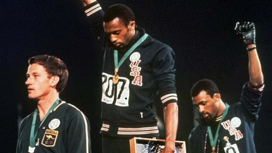 "Oct. 16, 1968: In this file photo, United States gold medalist Tommie Smith, center, and bronze medalist John Carlos, right, stare downward while extending their gloved hands skyward in racial protest alongside Australian silver medalist Peter Norman during the playing of ""The Star Spangled Banner""following the 200-meter race at the Mexico City Summer Olympics."