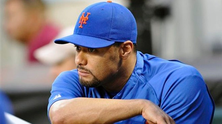 New York Mets pitcher Johan Santana watches from the dugout during the second inning of a baseball game against the Atlanta Braves on Friday, Aug. 10, 2012, in New York. (AP Photo/Bill Kostroun)