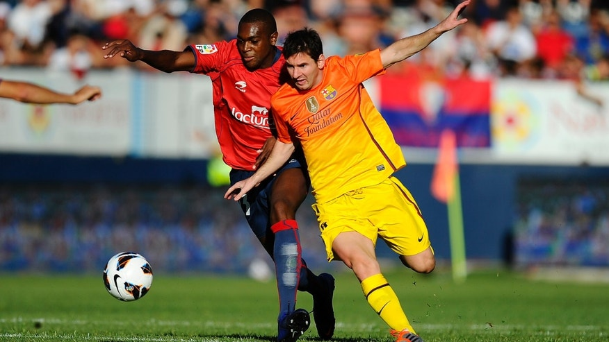 Lionel Messi of FC Barcelona (R) duels for the ball with Raoul Cedric 'Raoul Loe' of CA Osasuna during the La Liga match between CA Osasuna and FC Barcelona at Estadio Reyno de Navarra on August 26, 2012 in Pamplona, Spain.  (Photo by David Ramos/Getty Images)