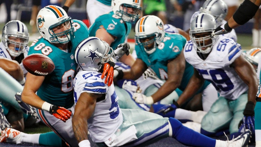 Aug. 29, 2012: Miami Dolphins tight end Jeron Mastrud (88) tangles with Dallas Cowboys linebacker Victor Butler (57) as the ball pops loose after a touchdown scored by Dolphins' Lamar Miller (not shown) during the third quarter of the NFL preseason football game, in Arlington, Texas.
